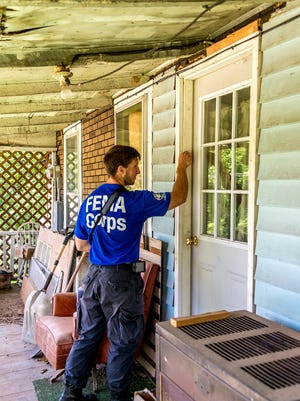 Manitowoc County native Kevin Schiman knocks on the door of a house with flood damage on July 13 in White Sulphur Springs, West Virginia.