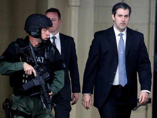 FILE - In this Dec. 5, 2016, file photo, Michael Slager, right, walks from the Charleston County Courthouse under the protection from the Charleston County Sheriff's Department after a mistrial was declared for his trial in Charleston, S.C. When nine black churchgoers in Charleston were massacred by Dylann Roof, a white man with Confederate sympathies, the city stayed calm and the victims' families offered examples of grace and forgiveness. Roof's guilty verdict came less than two weeks after a jury deadlocked in the case of Slager, a white ex-police officer charged with fatally shooting Walter Scott, a black man, as Scott tried to flee an April 2015 traffic stop.
