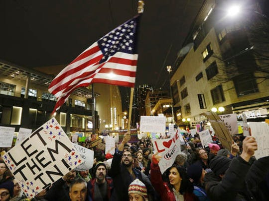 "FILE - In this Sunday, Jan. 29, 2017 file photo, a protester waves a U.S. flag as another holds a sign that reads ""Let Them In"" during a march and rally to oppose President Donald Trump's executive order barring people from certain Muslim nations from entering the United States, in downtown Seattle."