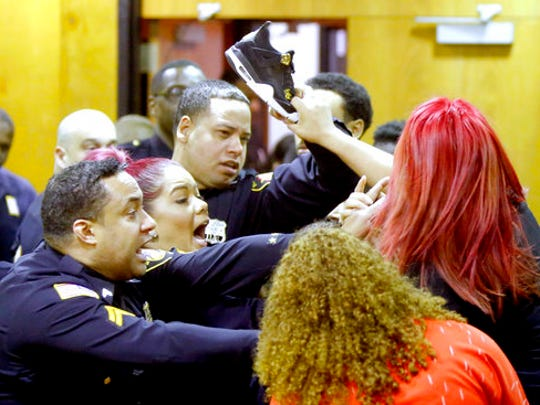 """Sheriff's Deputies keep Debora Hernandez, right, the mother of Antonio Vega's daughter, from hitting a defendant's family member with her shoe after an altercation between the two groups broke out at the end of a hearing where Clarence Williams and Gerry Thomas made their appearances for murder, Friday, March 24, 2017, in Paterson, N.J.  The two Paterson residents have been charged with murder in a double homicide involving a burning car owned by a woman who often appears on """"Real Housewives of New Jersey.""""  The pair are charged with killing Aaron Anderson and Antonio Vega Jr., who were found last week inside a burning 2015 Audi."""
