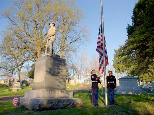 United State Marine Corp Staff Sgt. Kevin Harmon, left, and Pfc. David Aguirre raise the flag at Mount Mora Cemetery Thursday, April 6, 2017, in St. Joseph, Mo. They also laid a wreath at the World War I memorial in honor of the 100th anniversary of the United States entering the first world war.