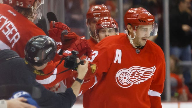 Nov 30, 2014; Detroit Red Wings center Pavel Datsyuk (13) celebrates with the bench after scoring in the second period against the Vancouver Canucks at Joe Louis Arena.
