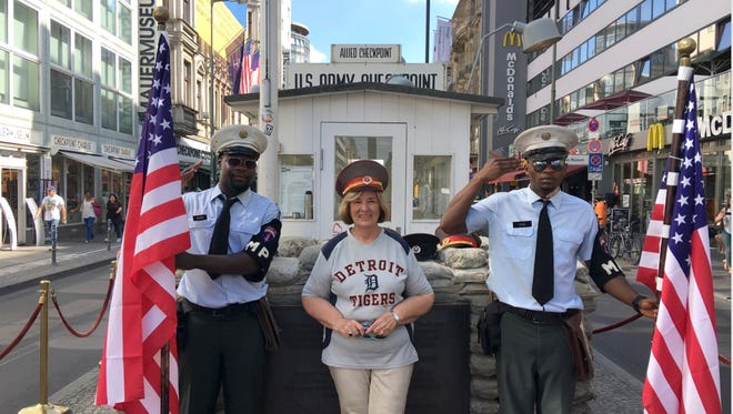 """Donna Economo of Farmington took the """"D"""" to Berlin, Germany in June of 2017. She visited Checkpoint Charlie with actors dressed as allied military policemen. She is wearing a Russian hat that one of the men gave her."""