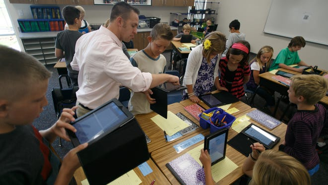 Crimson View Elementary School  teacher Steve Eves, top left, explains how to photograph and import a document onto an iPad as his students learn the ins and outs of their newly acquired technology on the first day of school in 2013.