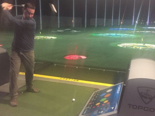 Matt Tapia takes a practice swing at the Topgolf Nashville