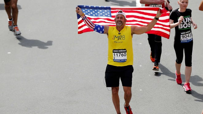 Frank Fumich of Arlington, VA holds an American flag as he crosses the finish line during the 2014 Boston Marathon.