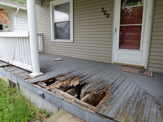 Part of the front porch of an abandoned house on O'Gara Avenue has rotted away. The house has been abandoned for at least two years, neighbors say.