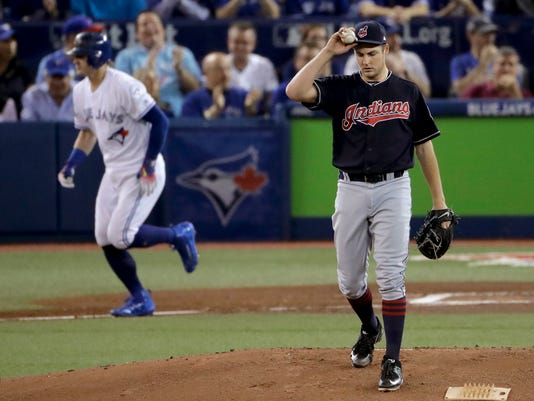 Cleveland Indians starting pitcher Trevor Bauer, right, walks Toronto Blue Jays Josh Donaldson during the first inning in Game 3 of baseball's American League Championship Series in Toronto, Monday, Oct. 17, 2016. (AP Photo/Charlie Riedel)