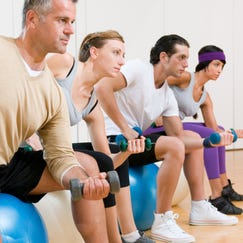 Healthy young people lifting dumbbell and sitting on a fitness ball at gym, instructor on foreground