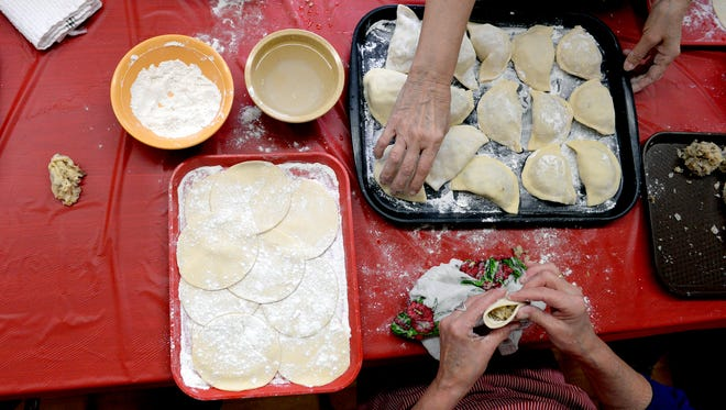 A discarded glob of dough didn't make the cut and sits to the side as Carol Pasichnyk, bottom, seals the edge of a pier—g as she and Joyce Brennan help make pierogi at the Polish Federated Home Tuesday, April 19, 2016 in Lansing in preparation for Pierogi Day.