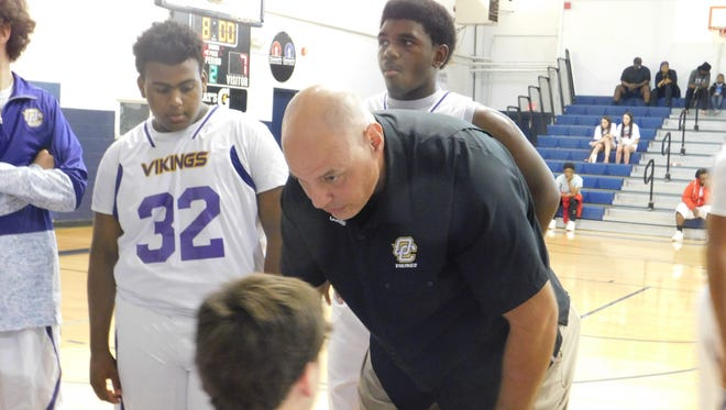 Opelousas Catholic boys' head basketball coach Jeff Dupre discusses strategy with his team on Friday afternoon during a game with Bunkie. The Vikings won their first game of the season with a 67-49 win.