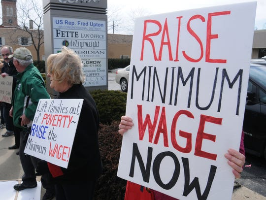 Residents gather during a minimum wage rally outside