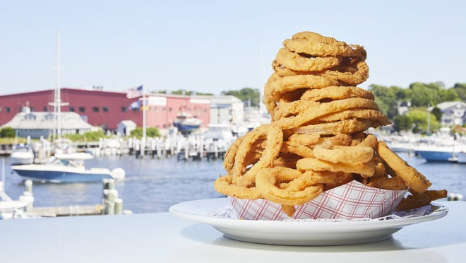 The Flying Bridge Restaurant's  hand-cut and breaded onion rings, shown here with Falmouth Harbor in the background, sell so well that staff goes through 200 to 300 pounds of onions per day.