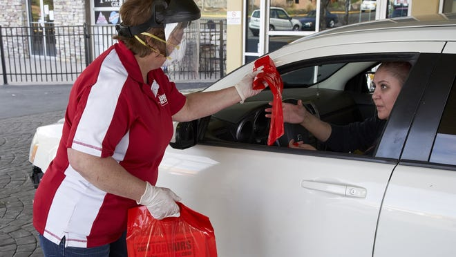 Job fair specialist Kathy Zywiec, left, hands out bags containing information about employers seeking help, during a drive-through job fair in Omaha, Nebraska, in April. Due to the coronavirus outbreak, the planned job fair where employers were to meet face to face with prospective candidates has been reconfigured to a drive-through event.