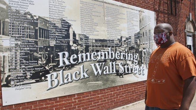 Freeman Culver stands in front of a mural listing the names of businesses destroyed during the Tulsa race massacre in Tulsa, Okla.,