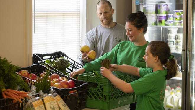 Jacki and Tim Hildreth, owners of Central Mass Locavore, and daughter Kaelyn load crates with fresh produce in their garage/warehouse. They have seen business explode in the last few months.