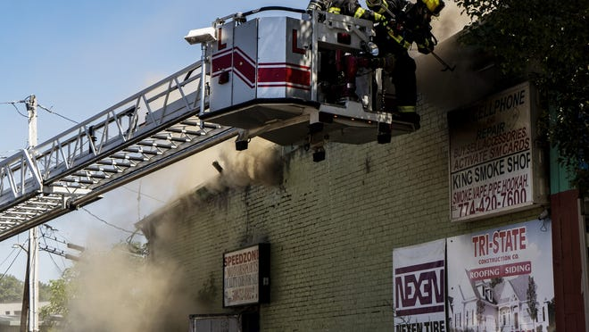 Firefighters battle a four-alarm fire at 1094-96 Main St. in Webster Square in Worcester on Tuesday.