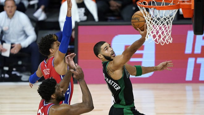 Boston's Jayson Tatum, right, goes up for a shot as Philadelphia's Joel Embiid (21) and Matisse Thybulle defend during the first half of Monday's game.