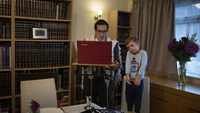 As his 3-year-old son Tzvi looks on, Rabbi Mordechai Chalk leads a service for his congregation via a teleconference app from his home in London on a Friday in June.