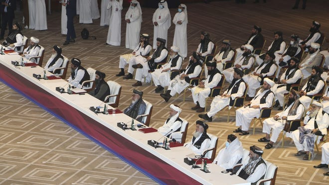 Taliban negotiator Abbas Stanikzai, fifth right, with his delegation attend the opening session of the peace talks between the Afghan government and the Taliban Saturday in Doha, Qatar.
