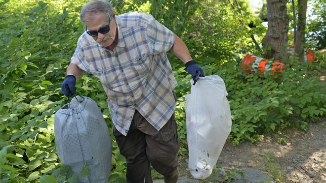 Bill Gilbert carries bags of trash out of the woods near Lake Quinsigamond's Herb Orcutt Memorial Landing on Lake Avenue in Worcester on Tuesday.