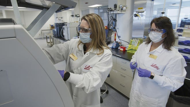 In this May photo provided by Eli Lilly, researchers prepare cells to produce possible COVID-19 antibodies for testing in a laboratory in Indianapolis.