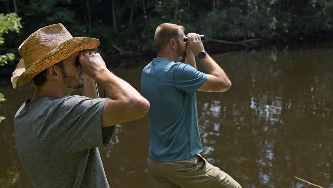 Brian Fay, left, and his brother, Mark Fay, search the Ware River in Barre for an elusive large snake on Tuesday.