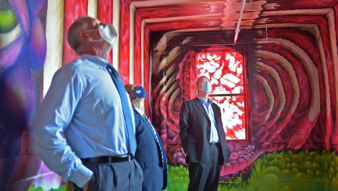 Dr. Eric Dickson, CEO and president of UMass Memorial Health Care; Douglas Brown, president of UMass Memorial Community Hospitals and Chief Administrative Officer, and Worcester City Manager Edward Augustus Jr. tour a room on the second floor of 2 Ionic Ave., being transformed into Creative Hub Worcester. The room was spray painted by an artist from New York.