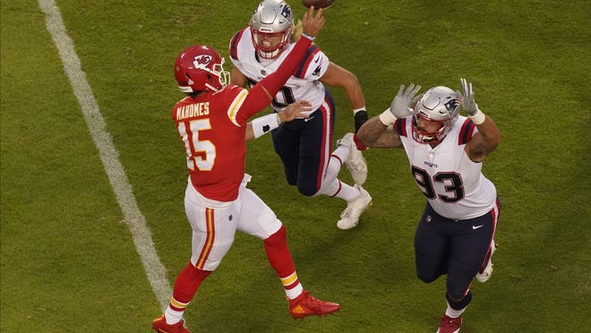 Kansas City quarterback Patrick Mahomes throws under pressure from New England's Chase Winovich and Lawrence Guy, right, during Monday's game.