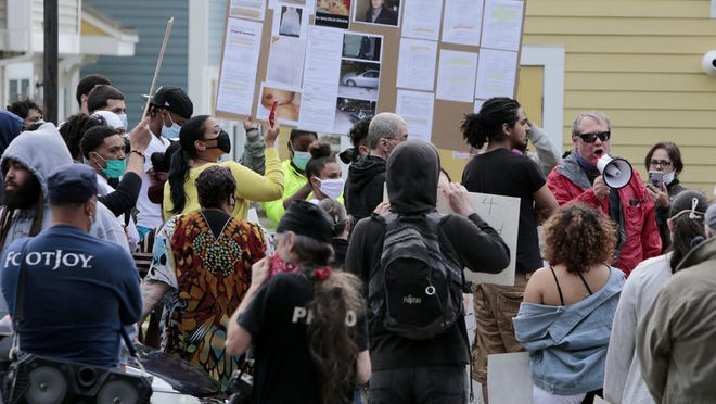 Protestors in June gathered at the site where Malcom Gracia was killed by police on Cedar Street in 2012. Don Brisson, an attorney for Gracia's family, speaks to the protesters about evidence he said contradcited the narrative in the police report.