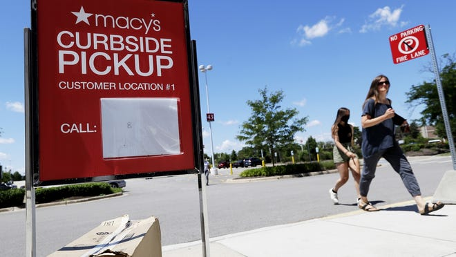 People walk past curbside pickup sign at Macy's department store in Vernon Hills, Illinois, in June.