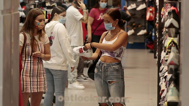 A shopper takes a look at some shoes on sale at Foot Locker at the Dartmouth Mall when it re-opened during the pandemic in March. Massachusetts state government has collected $372 million more in taxes from people and businesses than it did during the last six months of 2019.