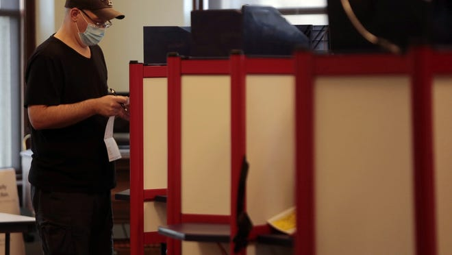 A voter wearing a mask takes a closer look at the options on his ballot while voting at the early voting polling station on the third floor of the downtown public libray in downtown New Bedford.