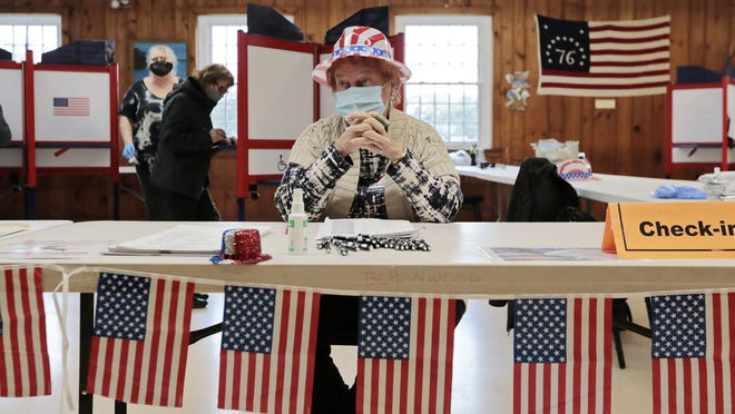 Poll workers get into the spirit of the 2020 presidential election Tuesday inside of the Buttonwood warming house polling station in New Bedford.