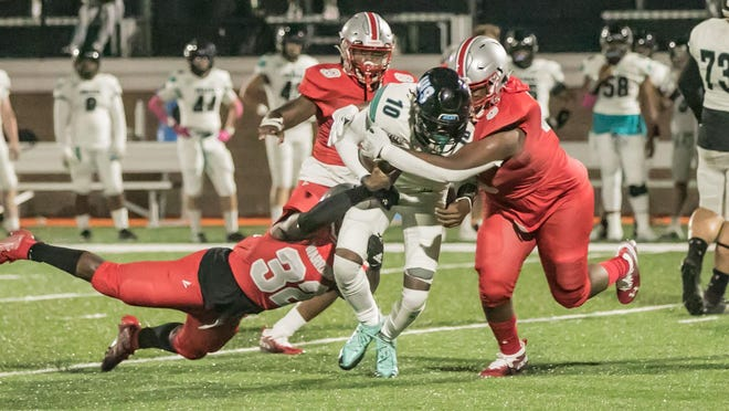 Islands senior quarterback Jadon Adams (10) is brought down by Jenkins High's Clarence Betterson (32) and JacQuez Williams (5) early in Friday's game at Memorial Stadium. Adams helped lead the Sharks to a 26-8 victory.