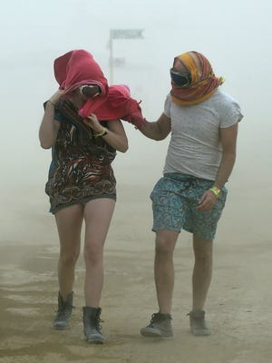 Robynne Rowlinson, left, and James Bisset, both from South Africa, walk through a morning dust storm at Burning Man on the Black Rock Desert, Nevada on Saturday, Aug. 29, 2015.
