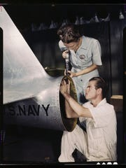 Mrs. Virginia Davis, a riveter in the assembly and repair department of the Naval Air Base, supervises Chas. Potter, a NYA trainee from Michigan; Corpus Christi, Texas. Image was taken in August 1942 by the Office of War Information and resides in the Library of Congress.