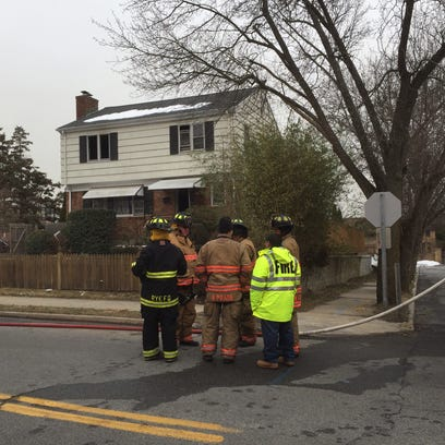 Firefighters stand at the scene of a house fire on