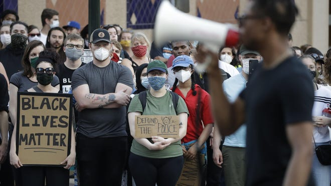 Demonstrators hold signs Saturday in the Country Club Plaza district of Kansas City. With COVID-19 continuing to infect about 200 new people daily, many who have participated in mass protests are wearing masks to limit spread of the coronavirus.