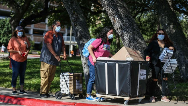 Alexis Hernandez pushes a cart as her family from left, Marie and Ralph Hernandez and her sister Jennifer Mendoza help her move Thursday into the San Jacinto Residence Hall at the University of Texas. A report from UT researchers projects between 82 students and 183 students could arrive on campus infected with the coronavirus.