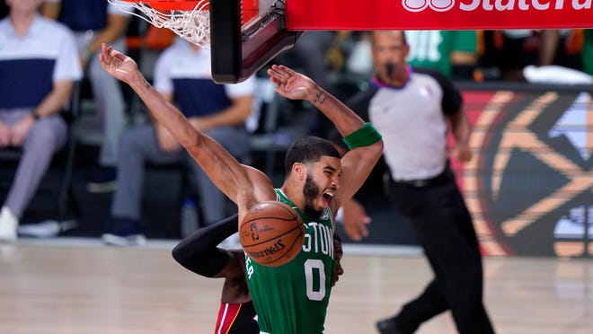 The Celtics' Jayson Tatum celebrates dunking in front of the Heat's Kendrick Nunn during the second half of Game 3 Saturday night.