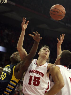 Marquette Golden Eagles guard Deonte Burton (30) fights for a rebound with Wisconsin Badgers forward Sam Dekker (15) as teammate Ben Brust (1) looks on during the first half at the Kohl Center.