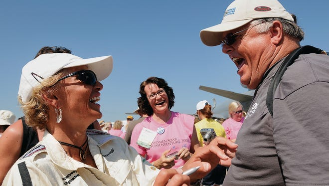Aerobatic pilot Patty Wagstaff, left, shares a hearty laugh with a fan while signing autograph after participating the most female pilots in one place gathering at AeroShell Square Friday, August 1, 2008 at EAA AirVenture in Oshkosh.  Oshkosh Northwestern Photo by Shu-Ling Zhou
