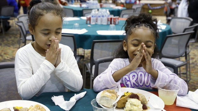 Dossani Taylor (left) and Saniyah Rico say a prayer before their meal during the Salvation Army's annual Christmas dinner at the Phoenix Convention Center on Sunday, Dec. 25, 2016.