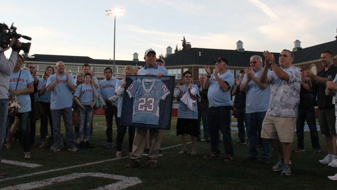 Former South Salem athlete, coach and athletic director Dave Johnson (middle) had his jersey retired on Friday, Sept. 18, 2015.