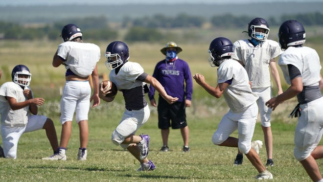 Thrall High School football players, wearing face masks at all times and using social distancing when possible, go through a practice Thursday in Thrall, Texas.