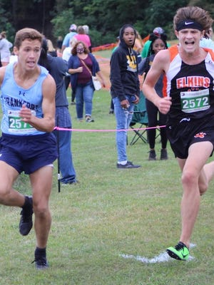 Frankfort's Garrett Ferguson eyeballs Elkins' Charlie Smoak as the two head to the finish line.  Ferguson would edge Smoak by inches, win the event, and set a new course record. Tribune photo by Chapin Jewell