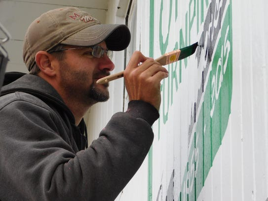 """Scott Hagan, shown painting the mural honoring the Ohio Turnpike's 60th anniversary as well as President Rutherford B. Hayes in October 2015, has just finished the third barn in the Sandusky County Visitors and Convention Bureau's """"barn trail."""""""