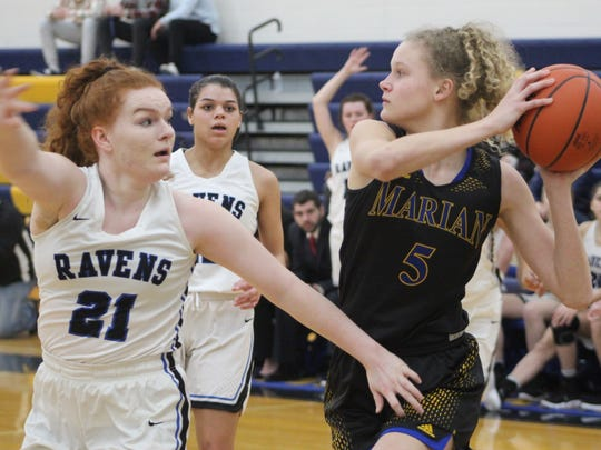 Marian's junior forward Megan  Kraus (5) grabs a first-half offensive rebound and is defended by Royal Oak junior Anna Ross (21).