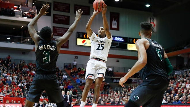 Cincinnati's Kevin Johnson (25) shoots against Tulane's Ray Ona Embo (3) and Cameron Reynolds (5) in the first half of an NCAA college basketball game, Sunday, Jan. 1, 2017, in Cincinnati.